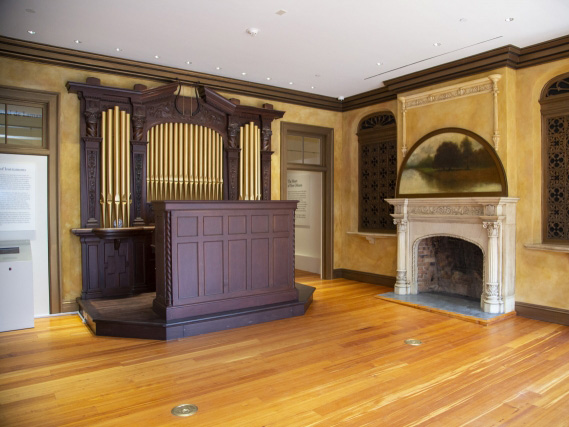 A restored 1920s pipe organ dominates an ochre-colored room that features ornate plaster screens and a grand fireplace.