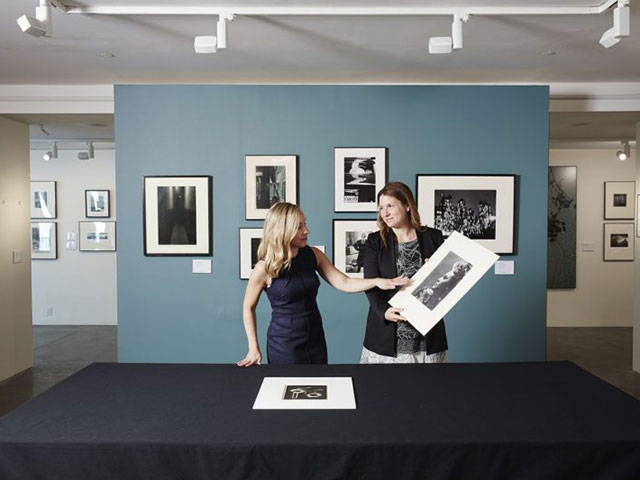 Worldwide Head of Photographs, Vanessa Hallett (right) holds up Dora Maar's Portrait de profil à la coiffure en hauteur with Head of Department Sarah Krueger in conversation.