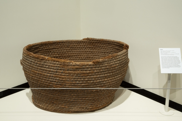 """A woven brown basket is featured in the exhibition """"Pieces of History"""""""