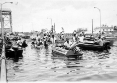 Evacuees from the Lower Ninth Ward are shown crossing the Judge Seeber (N. Claiborne Ave.) Bridge by foot and boat after Hurricane Betsy in 1965.