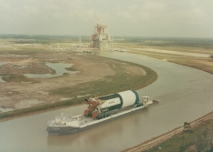 A Saturn V rocket is transported on a canal near a NASA testing facility